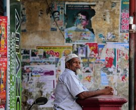 A Sri Lankan Muslim man leans against a letter box as he waits out side a closed shop during a shut down protest in Colombo, Sri Lanka, Thursday, June 19, 2014. Muslims have shut down their shops in Sri Lanka's capital to protest attacks by hard-line Buddhists on Muslims and are demanding the government punish those responsible for the violence. (AP Photo/Eranga Jayawardena)