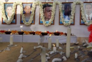 Candles are burnt in front of the photographs of 17 slain humanitarian workers from the French aid group Action Contre La Faim at their memorial in Batticaloa, Sri Lanka, August 11, 2006.  © 2006 Reuters